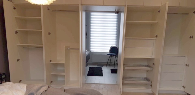 Dressing blanc avec porte en verre, accès salle de bain, tiroirs, penderies, tablettes extractibles