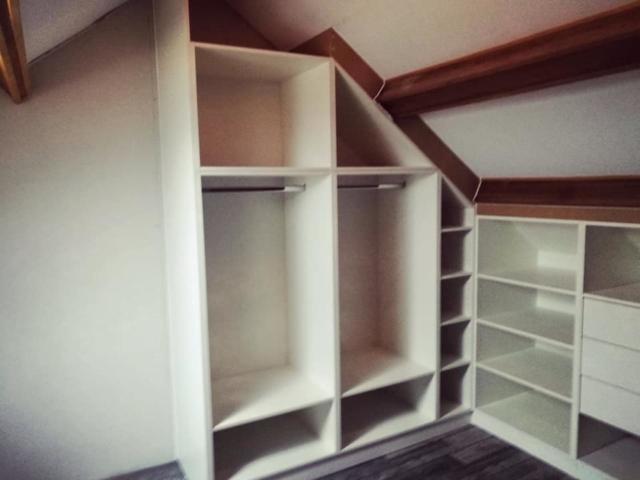 Aménagement d'un grenier avec des meubles en sous-pente, tringles, penderie pour plus de rangements
